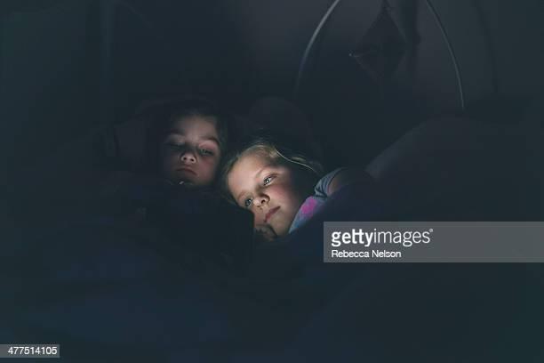 Girls watching electronic tablet in dark room