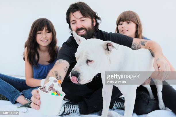 Girls watching father giving ice cream to dog