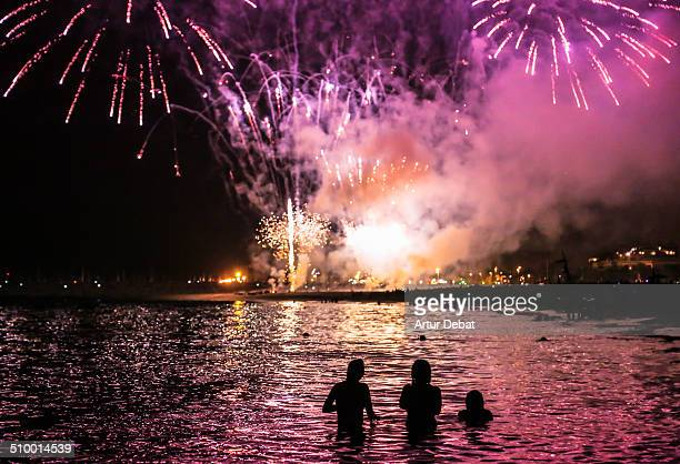 Girls watching fireworks from the water at summer