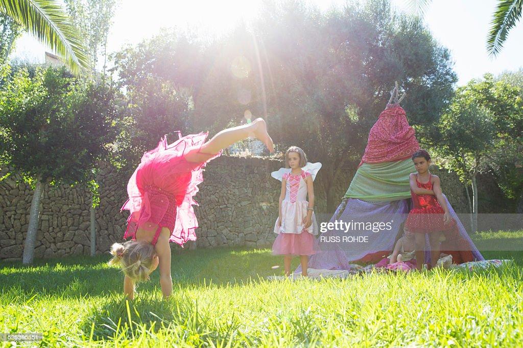 Girls watching friend in fairy costume doing handstand in garden : Stock Photo