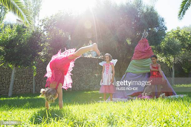 girls watching friend in fairy costume doing handstand in garden - girl in dress doing handstand stockfoto's en -beelden
