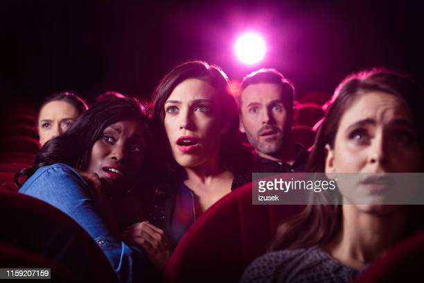 girls watching horror movie in cinema - action movie stock pictures, royalty-free photos & images