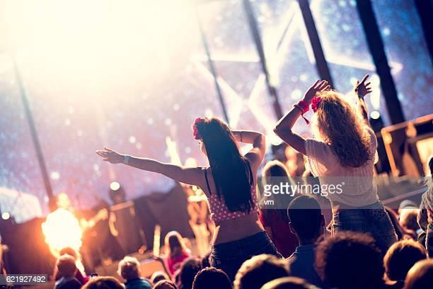 Girls waving hands sitting on shoulder at a concert