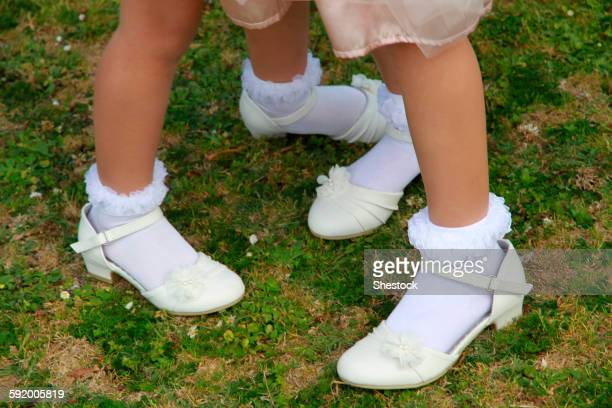 Girls wearing dress shoes and socks in grass