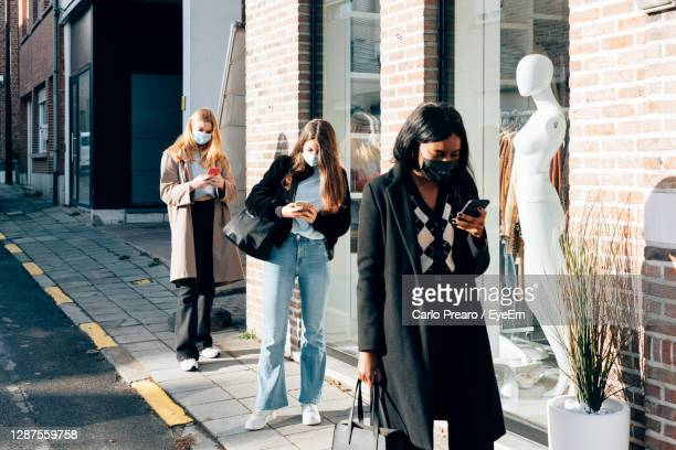 girls wearing face mask using a mobile phone while waiting on the street the opening of retail - lining up stock pictures, royalty-free photos & images