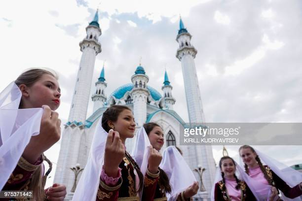 Girls wearing in Caucasian national dresses pose in front of the Qol Sharif mosque in the Kazan Kremlin in central Kazan on June 15 during of the...