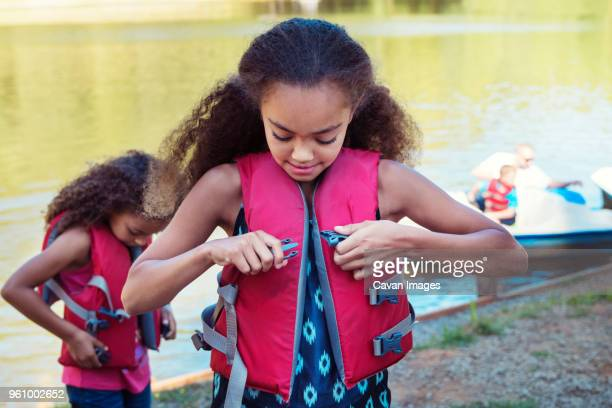 girls wearing life jackets while standing at lakeshore - life jacket stock pictures, royalty-free photos & images