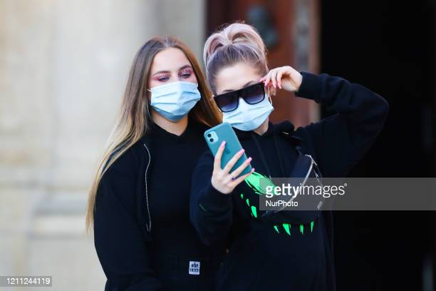 Girls wearing protective face masks due to the spread of coronavirus are seen taking selfies at the Main Square in Krakow, Poland on April 28, 2020....
