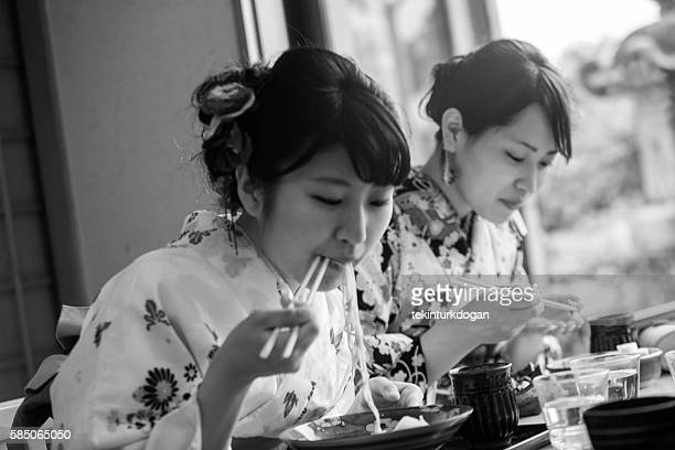 girls wearing traditional kimono costume eating noodle in kyoto japan