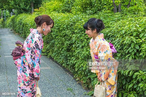 girls wearing traditional kimono costume  saluting eachother at  kyoto japan