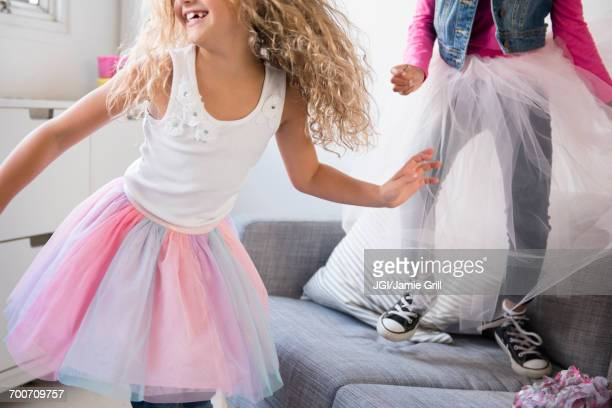 Girls wearing tutus dancing on sofa