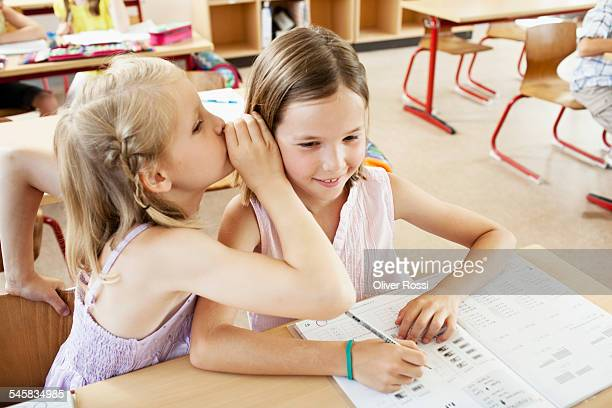 Girls whispering in classroom