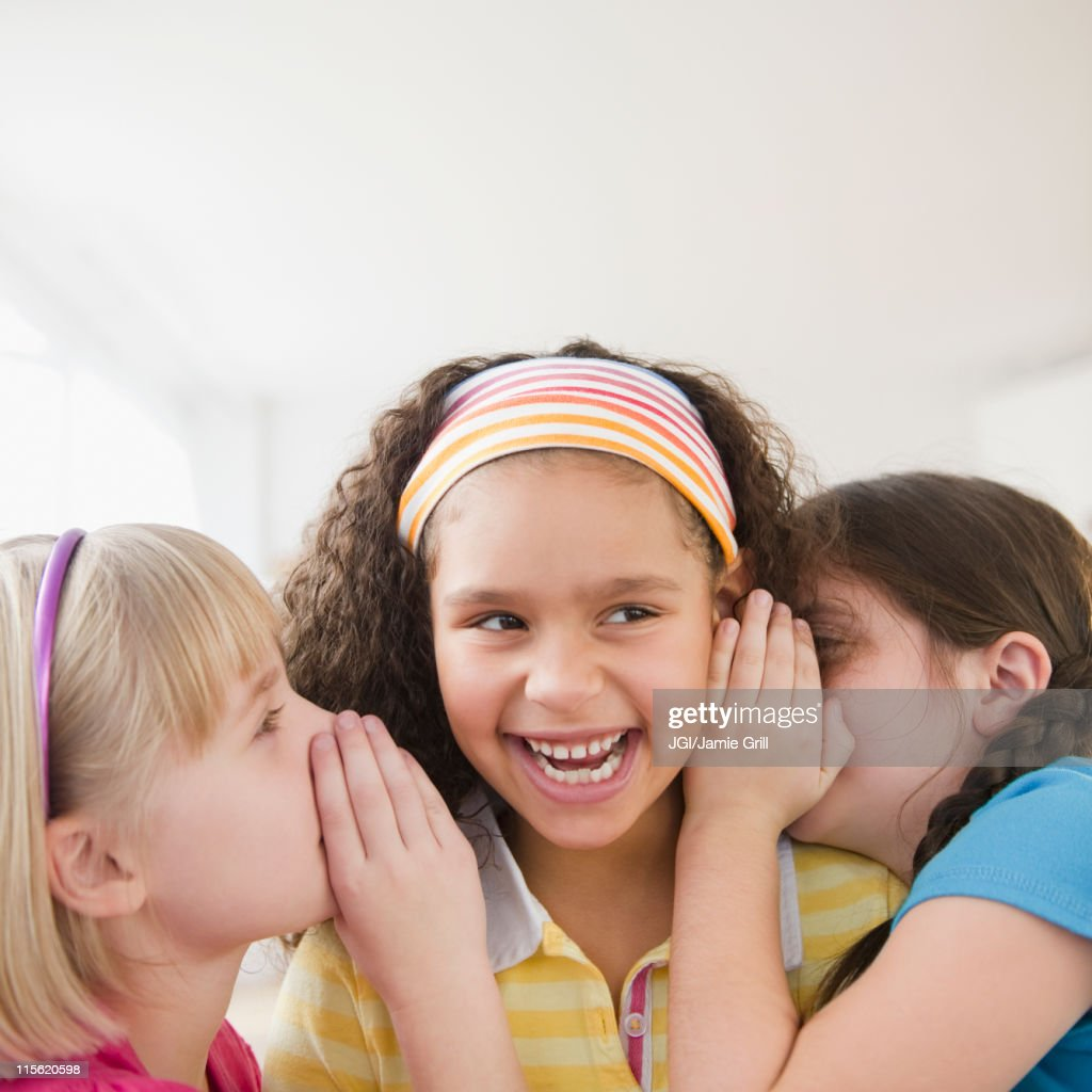 Girls whispering together : Stock Photo