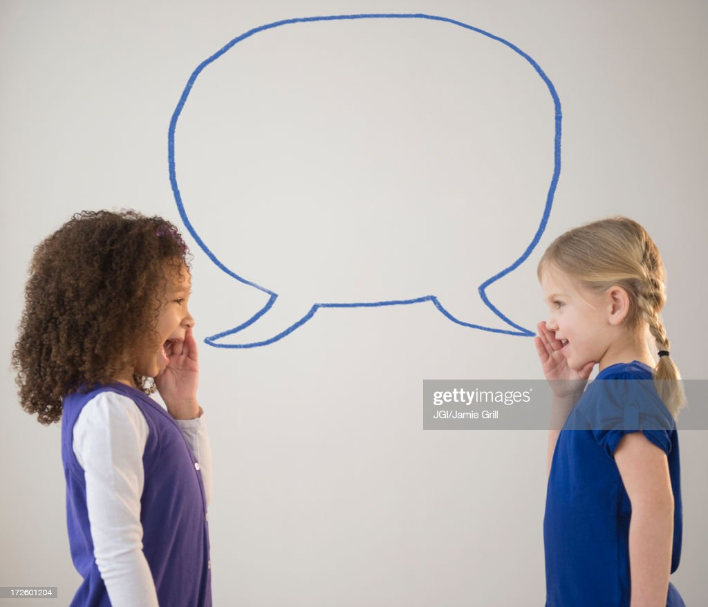 Girls whispering with empty speech bubble : Stock Photo