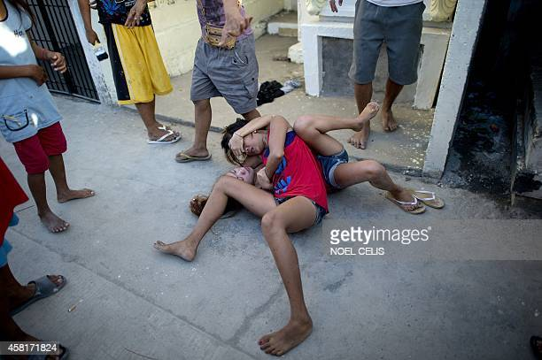 Girls who live inside the cemetry lie on the ground as they fight biting scratching each other's faces and pulling hair at the Navotas Public...