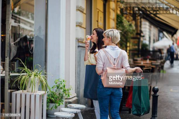 girls window shopping and having ice cream - ice cream parlour stock pictures, royalty-free photos & images