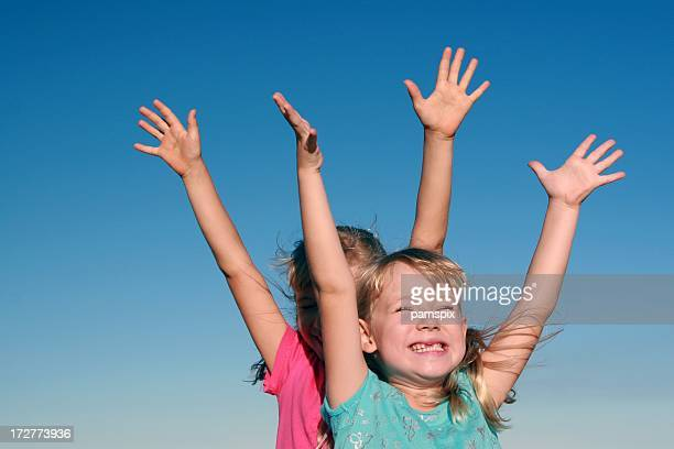 Girls with arms raised on blue sky background