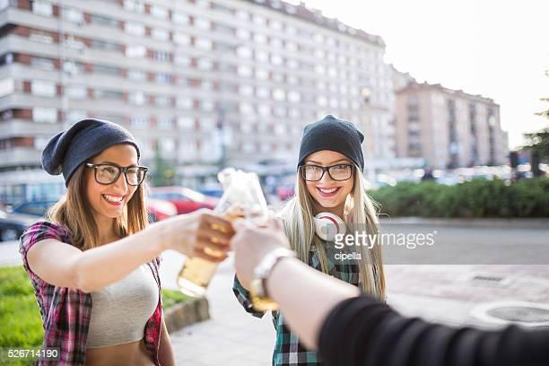 Filles avec des bouteilles de bière un toast à leur amitié en plein air