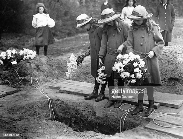 Girls with bunches of flowers stand over an open grave during the funeral of the victims of an air raid during World War I