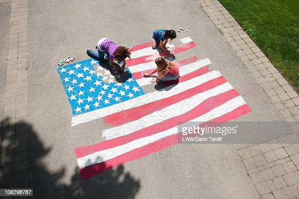 girls with chalk coloring american flag on sidewalk - independence day stock pictures, royalty-free photos & images