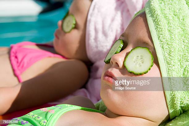 Girls with cucumber slices on eyes