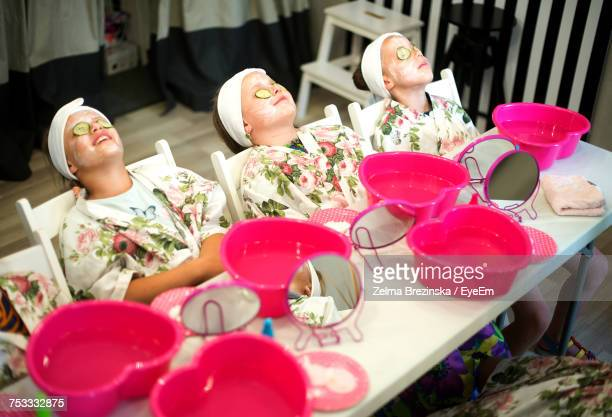 Girls With Facial Mask Relaxing By Table At Spa