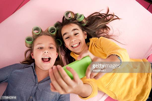 Girls with hair rollers photographing self with smartphone