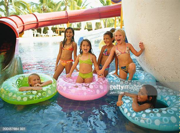 Girls (6-10) with inner tubes in swimming pool