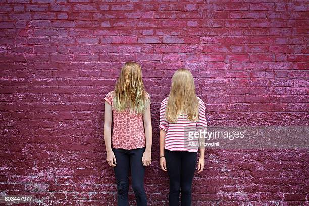 2 girls with long hair covering face against wall