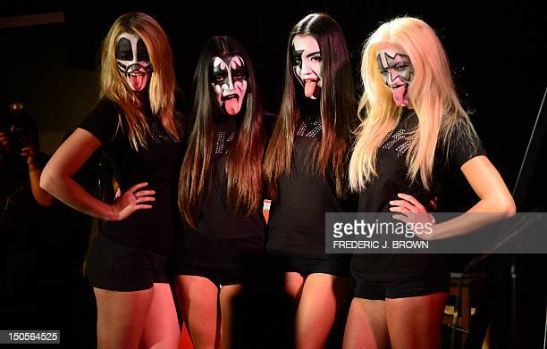 Girls with makeup on stage stick their tongues out impersonating the Rock band KISS as band members while awaiting the arrival of Gene Simmons Paul...