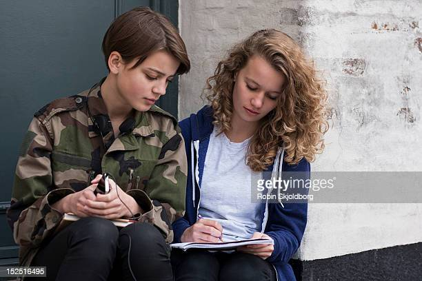 Girls with mobile taking notes