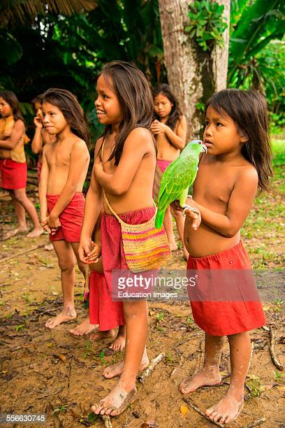 Girls with parrot in a village on the Amazon River Peru