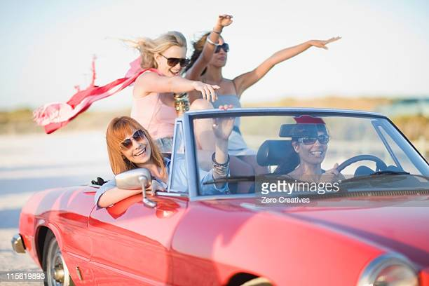 Girls with red scarf riding in cabriolet