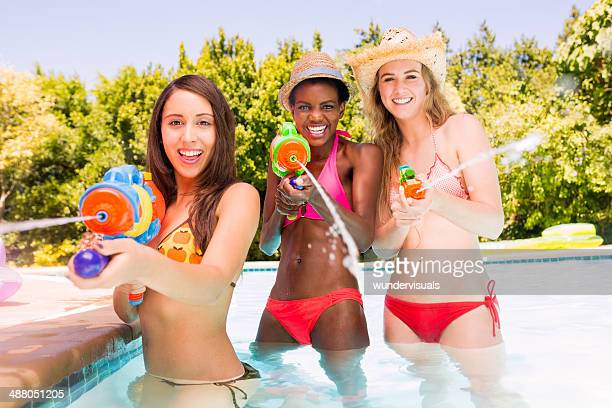 Filles avec Pistolet à eau dans la piscine