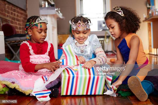 Girls with tiaras opening gifts at party
