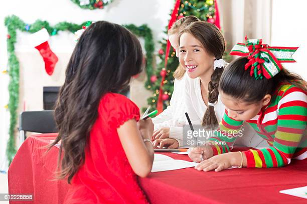 Girls work on creating Christmas cards for charity