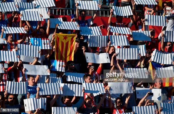 Girona fan holds a proindependence Catalan flag as others hold up placards to form a mosaic before the Spanish league football match Girona FC vs...