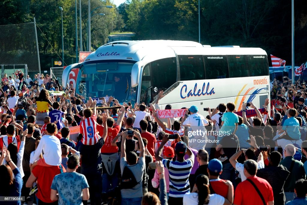 Girona FC and Real Madrid football fans gather around the bus carrying the Real Madrid team and staff upon their arrival for the Spanish league football match Girona FC vs Real Madrid CF at the Montilivi stadium in Girona on October 29, 2017. Hot on the heels of a historic few days in Catalonia after separatist leaders voted in favour of a unilateral declaration of independence, Real Madrid arrived to the region to face Girona. / AFP PHOTO / Josep LAGO