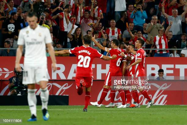 Girona players celebrate teammate Girona's Spanish midfielder Borja Garcia's opening goal during the Spanish league football match between Girona FC...