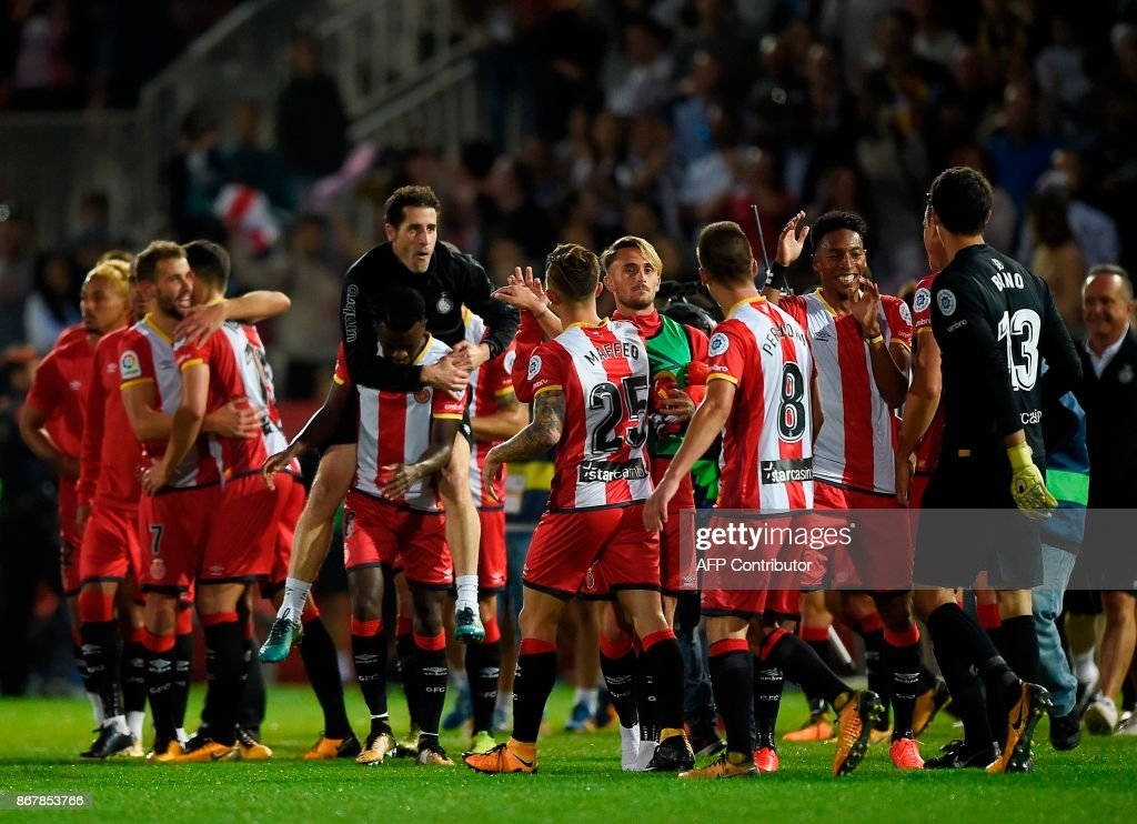 Girona players celebrate winning Real Madrid at the end of the Spanish league football match Girona FC vs Real Madrid CF at the Montilivi stadium in Girona on October 29, 2017. / AFP PHOTO / Josep LAGO