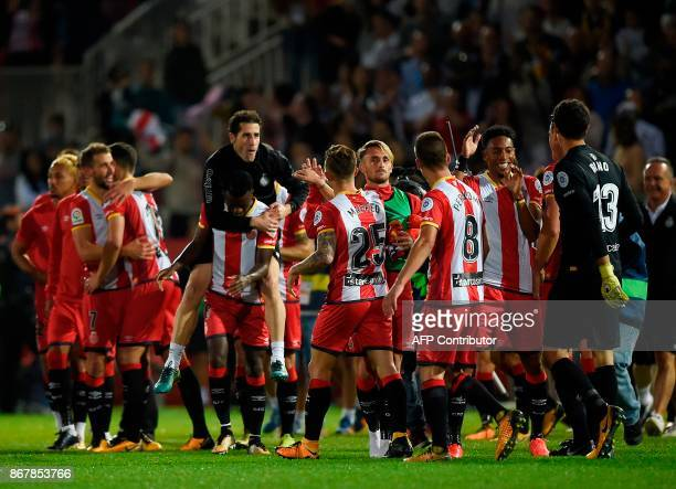 Girona players celebrate winning Real Madrid at the end of the Spanish league football match Girona FC vs Real Madrid CF at the Montilivi stadium in...