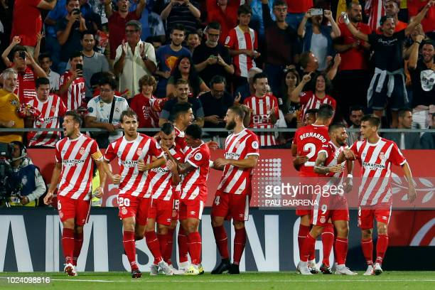 Girona players congratulate teammate Girona's Spanish midfielder Borja Garcia after scoring the opening goal during the Spanish league football match...