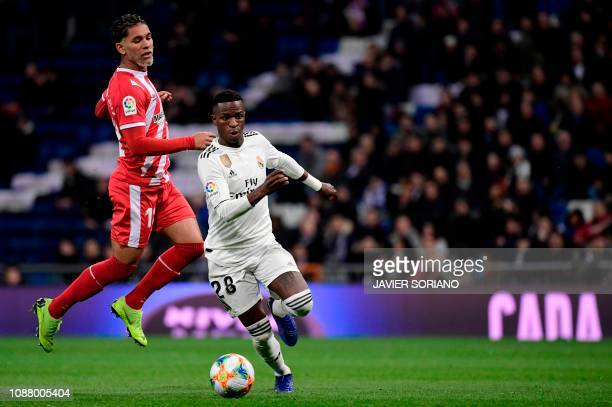 Girona's Brazilian midfielder Douglas Luiz vies for the ball with Real Madrid's Brazilian forward Vinicius Junior during the Spanish Copa del Rey...