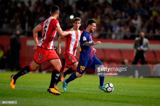 Girona's defender Juanpe Ramirez vies with Barcelona's forward from Argentina Lionel Messi during the Spanish league football match Girona FC vs FC...