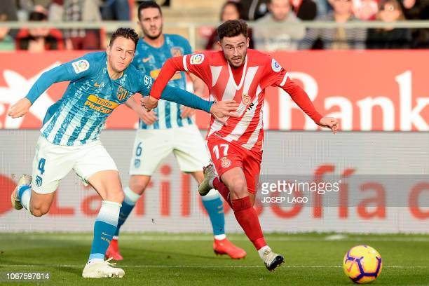 Girona's English midfielder Patrick Roberts challenges Atletico Madrid's Colombian defender Santiago Arias during the Spanish league football match...