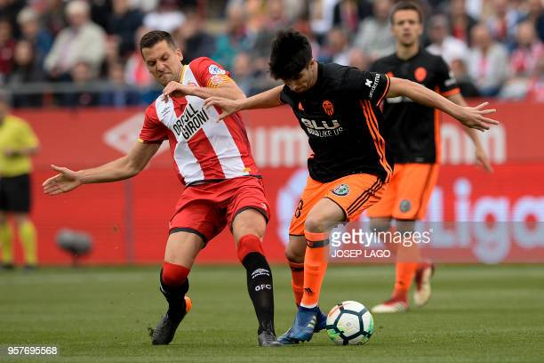 Girona's midfielder Alex Granell vies with Valencia's midfielder Carlos Soler during the Spanish league football match Girona FC vs Valencia CF at...