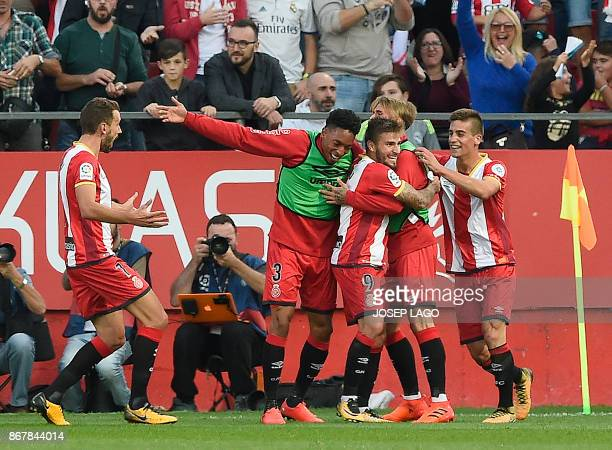 Girona's midfielder Cristian Portugues is congratulated by teammates after scoring a goal during the Spanish league football match Girona FC vs Real...