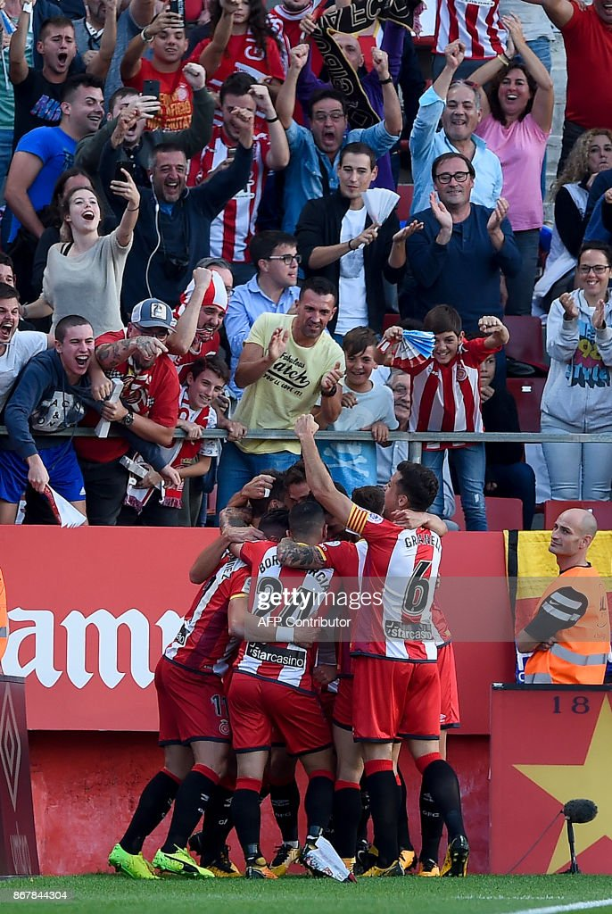 Girona's midfielder Cristian Portugues (C) is congratulated by teammates after scoring a goal during the Spanish league football match Girona FC vs Real Madrid CF at the Municipal de Montilivi stadium in Girona on October 29, 2017. / AFP PHOTO / Josep LAGO