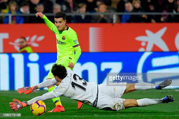 Girona's Moroccan goalkeeper Yassine Bounou dives to stop a shot on goal by Barcelona's Brazilian midfielder Philippe Coutinho during the Spanish...