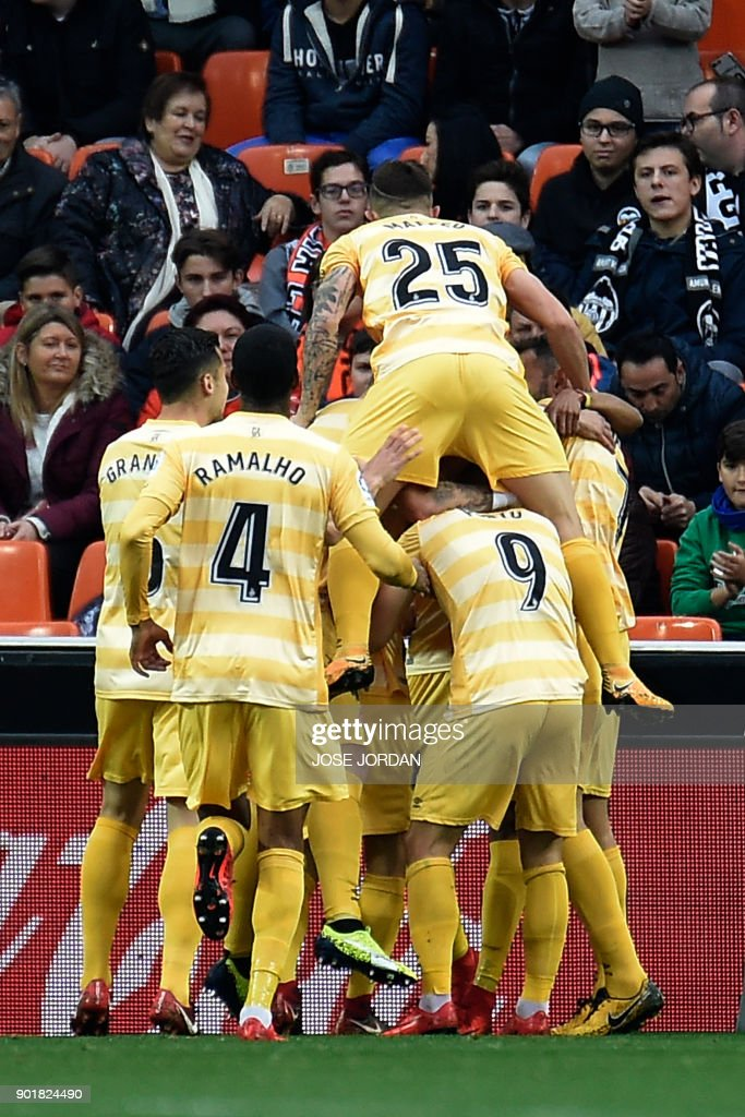 Girona's players celebrate after scoring a goal during the Spanish league football match between Valencia and Girona at the Mestalla stadium in Valencia on January 6, 2018. /
